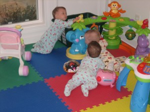 Evie, Maggie, and Josh are playing on their nine month birthday!
