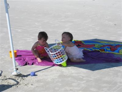 Maggie and Evie playing under the umbrella.