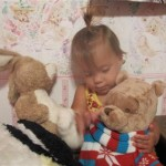 Evie loves to snuggle with the teddy bears!